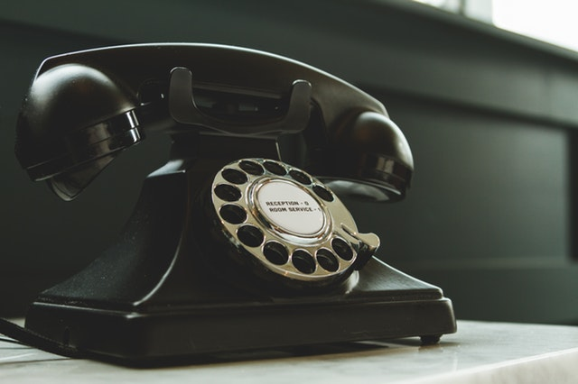 black-rotary-telephone-on-white-surface
